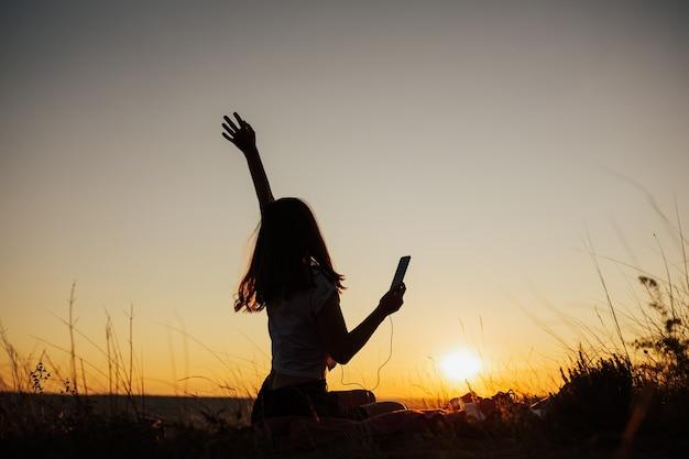 Garota feliz com a mão cantando e ouvindo música em fones de ouvido em um campo ao pôr do sol incrível.