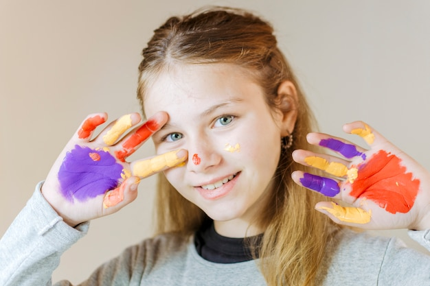 Garota feliz com as mãos pintadas em tinta aquarela