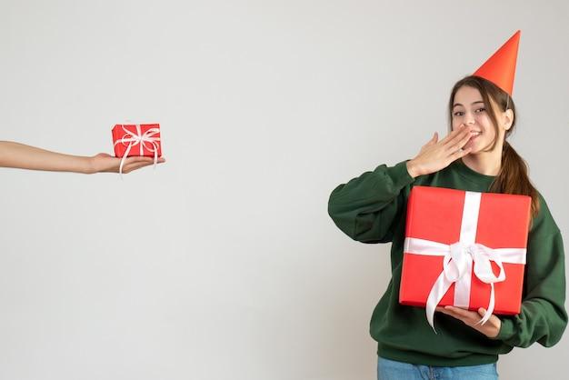 Garota feliz com boné de festa segurando seu presente de natal