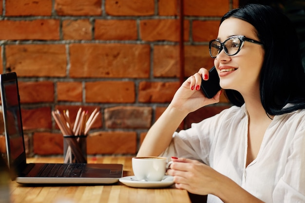 Garota feliz com cabelo preto, usando óculos, sentado no café com laptop, telefone celular e uma xícara de café, conceito freelance, retrato, cópia espaço, camisa branca.