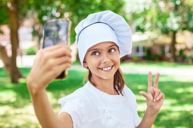 Garota feliz com chapéu de chef fazendo selfie