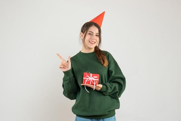 Garota feliz com chapéu de festa apontando para algo em branco