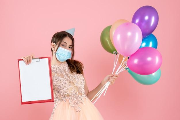 Garota feliz com chapéu de festa e máscara médica segurando balões coloridos e um documento rosa