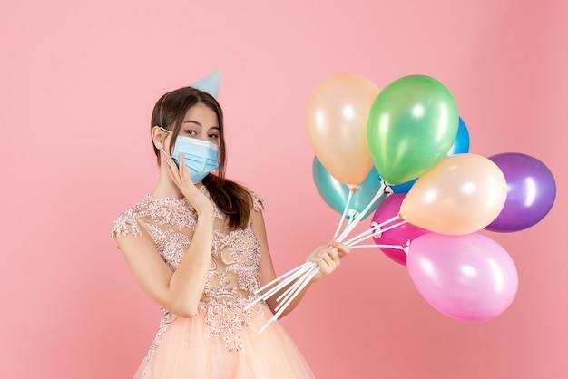 Garota feliz com chapéu de festa e máscara médica segurando balões coloridos em rosa
