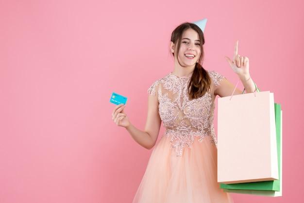 Garota feliz com chapéu de festa segurando cartão e sacolas de compras rosa