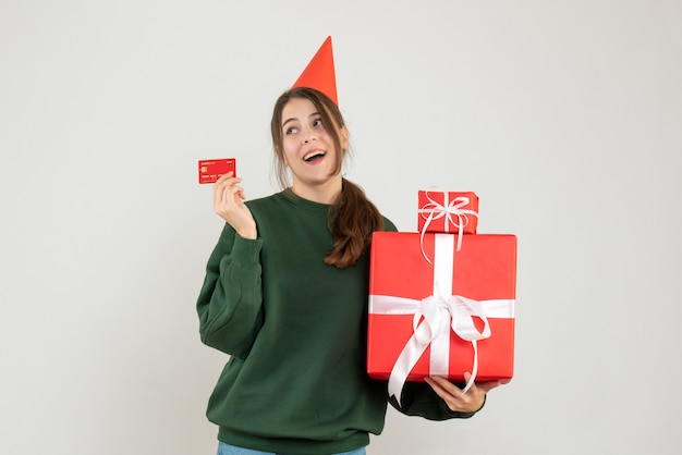 Garota feliz com chapéu de festa segurando presentes e cartão em branco