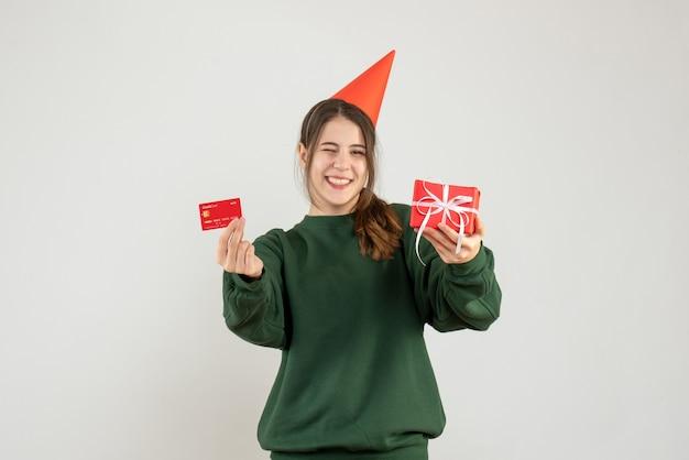Garota feliz com chapéu de festa segurando um cartão e um presente de natal em branco