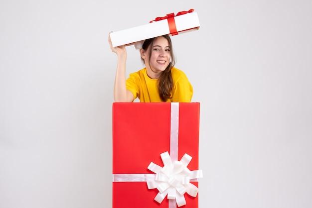 Garota feliz com chapéu de papai noel em pé na grande caixa de presente