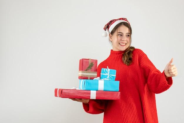 Garota feliz com chapéu de papai noel fazendo uma placa com o polegar segurando seu presente de natal
