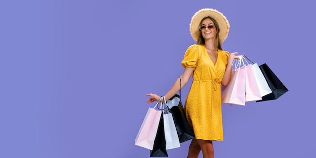 Garota feliz com chapéu e óculos escuros faz compras em fundo roxo preto, grandes vendas de sexta-feira