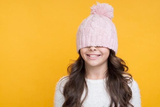 Garota feliz com chapéu rosa sobre os olhos