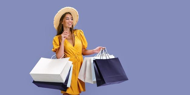 Garota feliz com chapéu segurando óculos de sol e compras enquanto sorri para a câmera preta nas grandes vendas de sexta-feira