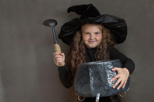 Garota feliz com fantasia de bruxa de halloween fazendo uma porção