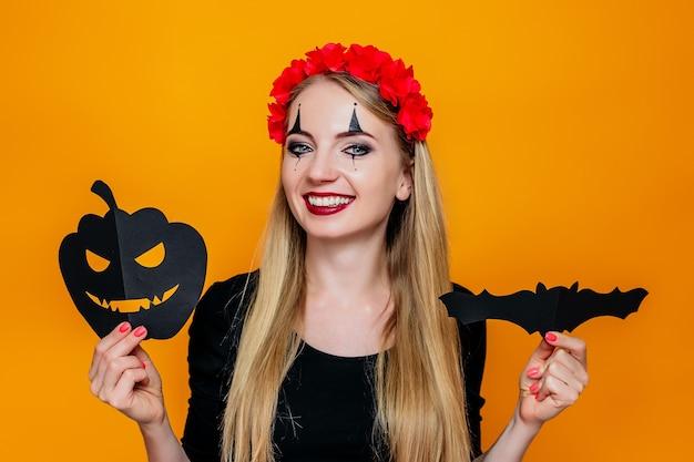 Garota feliz com fantasia de halloween segurando abóbora e morcego decorações de papel festivas isoladas em laranja