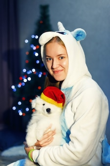 Garota feliz com fantasia de unicórnio e cachorro husky samoiedo em decorações de natal