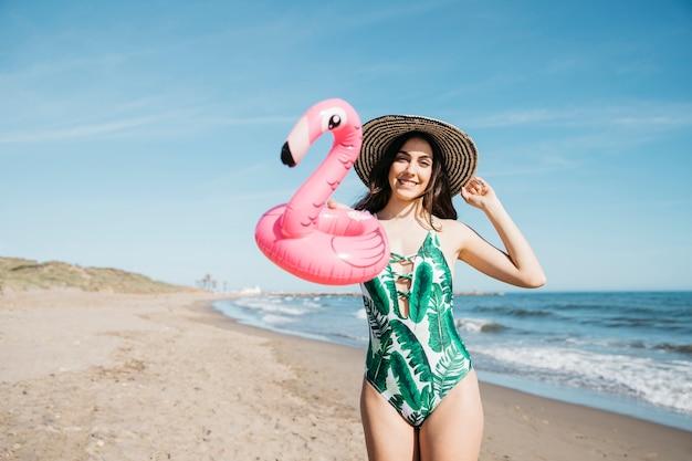 Garota feliz com flamingo inflável