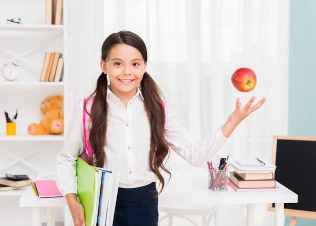 Garota feliz com mochila jogando a maçã