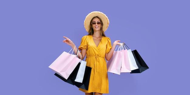 Garota feliz com óculos de sol de chapéu de palha faz compras enquanto sorri para a câmera preta.