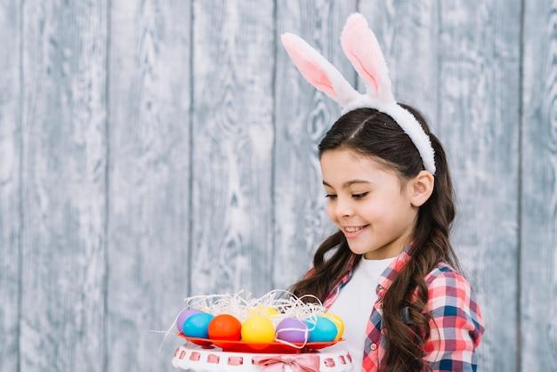 Garota feliz com orelhas de coelho olhando ovos de páscoa coloridos contra a mesa de madeira