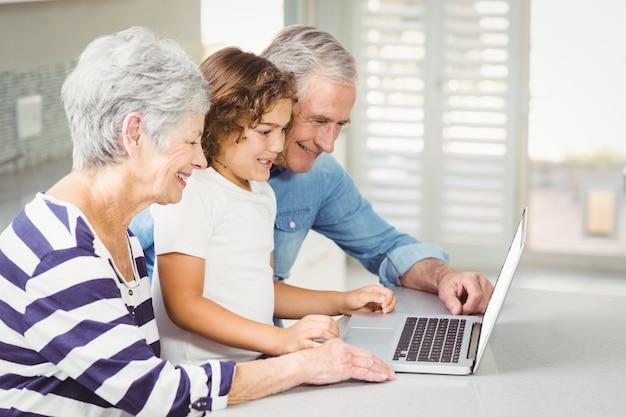 Garota feliz com os avós usando laptop