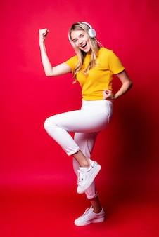Garota feliz com, ouvindo música em fones de ouvido e dançando, segurando um smartphone. em uma parede vermelha.