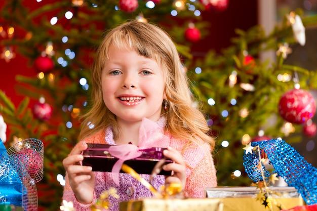 Garota feliz com presente de natal na véspera de natal