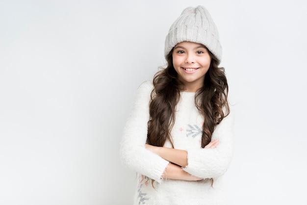 Garota feliz com roupas de inverno e mãos cruzadas