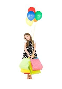Garota feliz com sacolas de compras e balões na parede branca