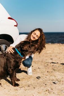 Garota feliz com seu cachorro na praia