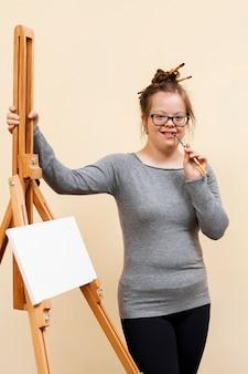 Garota feliz com síndrome de down, posando ao lado de cavalete