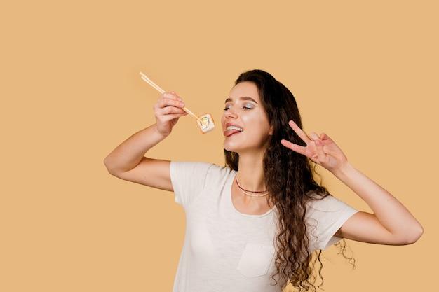 Garota feliz com sushi em fundo amarelo