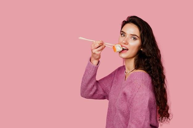 Garota feliz com sushi em fundo rosa