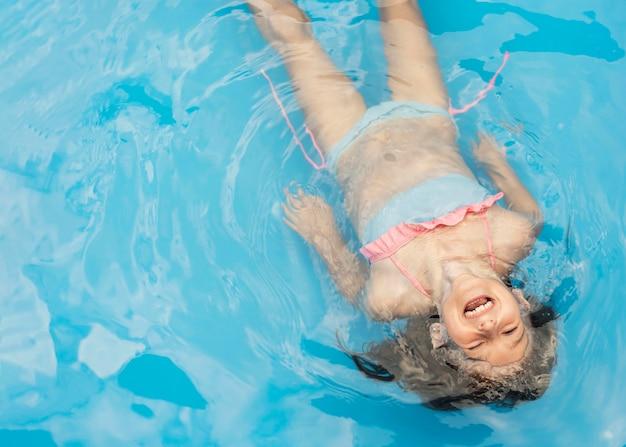 Garota feliz com tiro médio na piscina