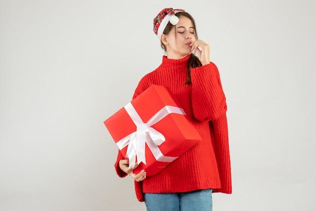 Garota feliz com um chapéu de papai noel segurando um presente fechando os olhos