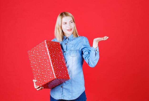 Garota feliz com um presente de pé no vermelho
