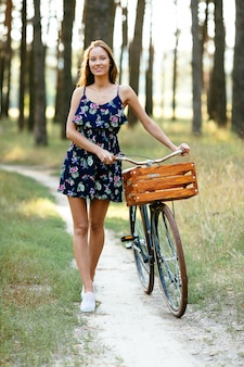 Garota feliz com uma bicicleta na floresta.