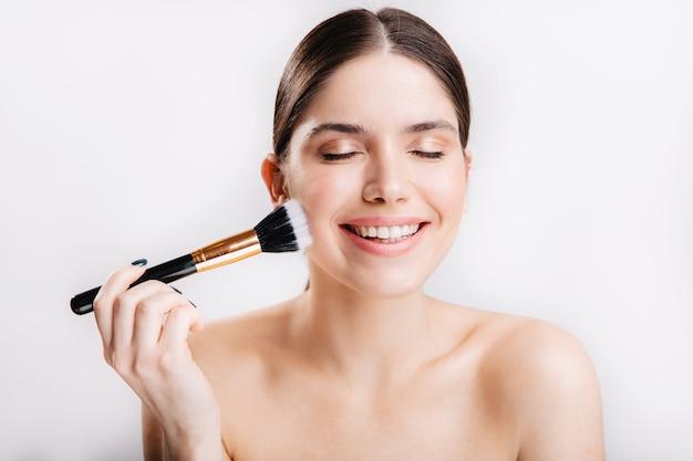 Garota feliz com uma pele saudável perfeita está sorrindo e tocando seu rosto com o pincel na parede branca.