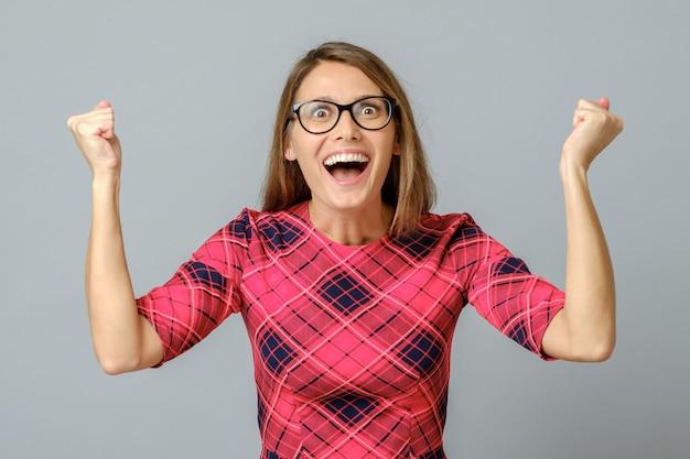 Garota feliz comemorando seu sucesso com os braços erguidos
