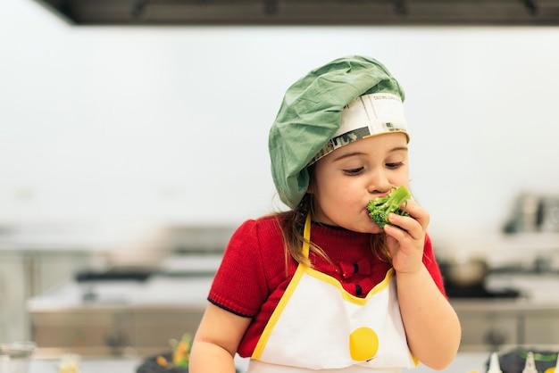 Garota feliz comendo brócolis na cozinha.