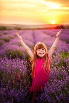 Garota feliz correndo no campo de lavanda