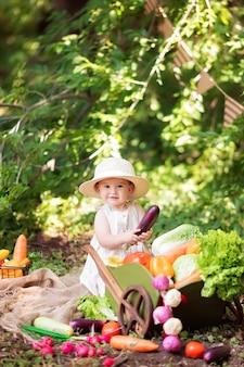 Garota feliz cozinha salada de legumes na natureza. um pequeno jardineiro recolhe uma colheita de vegetais.