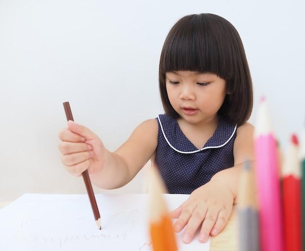 Garota feliz criança asiática, desenho com lápis de cor.
