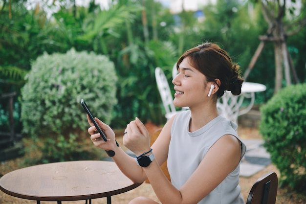 Garota feliz curtindo música em airpods e cantando sua música favorita, relaxando no jardim