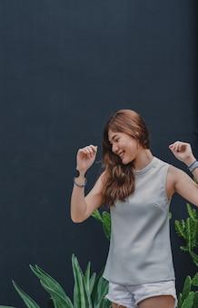 Garota feliz curtindo música em airpods e dançando a música favorita, viagem relaxante para fora.