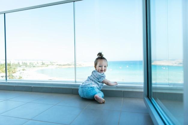 Garota feliz da criança olhando para chipre, mar mediterrâneo, de um balcão de vidro