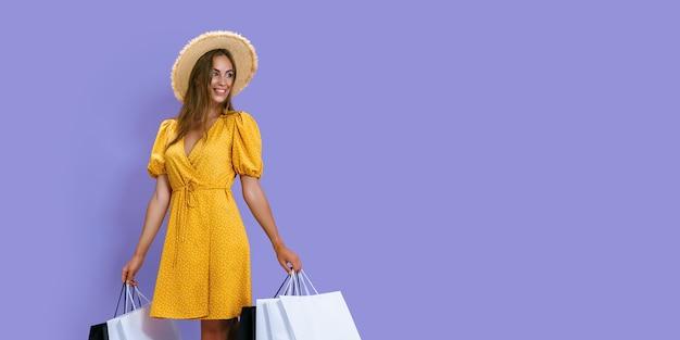 Garota feliz da moda guarda pacotes depois de comprar no fundo roxo com desconto em vendas de sexta-feira negra