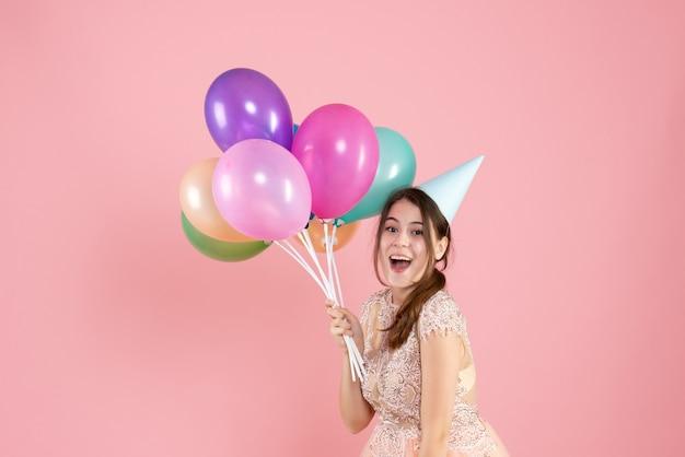 Garota feliz de frente com boné de festa segurando balões coloridos