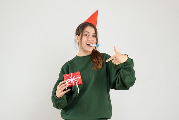 Garota feliz de frente com chapéu de festa apontando para seu presente de natal