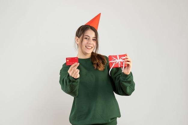 Garota feliz de frente com chapéu de festa segurando o presente e o cartão