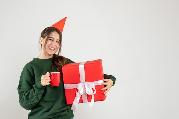 Garota feliz de frente com chapéu de festa segurando seu presente de natal e copo